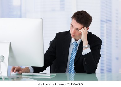Worried young businessman looking at computer at office desk