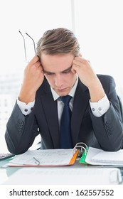 Worried young businessman looking down at documents in office