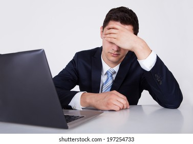 Worried young businessman looking at laptop at desk against white background