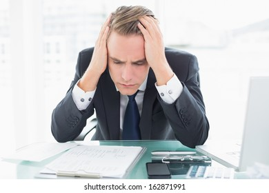 Worried young businessman sitting with head in hands at office desk