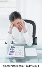 Worried young businesswoman with graphs sitting at office desk