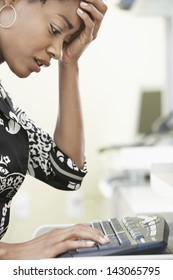 Worried young businesswoman typing on computer keyboard in office