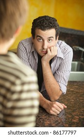 Worried young Caucaisian man with hand on chin in kitchen