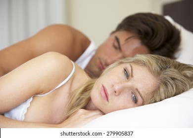 Worried Young Couple In Bed