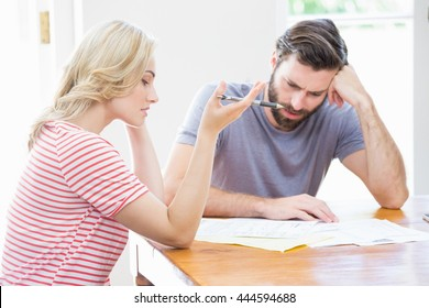 Worried young couple checking on bills at home