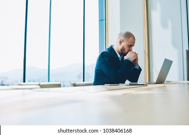 Worried young entrepreneur thinking about solving financial problems working at laptop computer sitting in office building. Pensive male executive manager looking stressful while making decisions