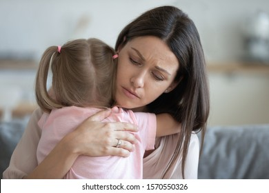 Worried young foster care parent mother comforting solacing embrace adopted little child daughter give care and protection at home, loving concerned adult mom hug sad small girl consoling kid concept