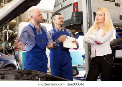 Worried young girl talking with specialists at auto repair shop. Focus on the left man