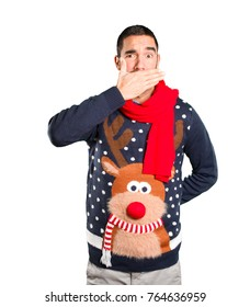 Worried young man on Christmas covering his mouth with his hands