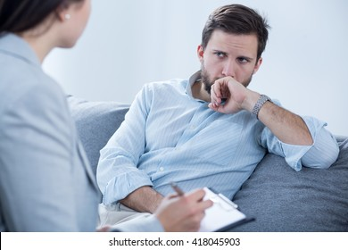 Worried young man on psychotherapy with doctor