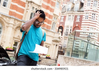 worried young man reading a letter in the street