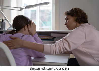 Worried young mother talking comforting upset teen daughter helping with problem or apologizing at home. Caring parent mum consoling depressed adolescent child giving psychological support concept.