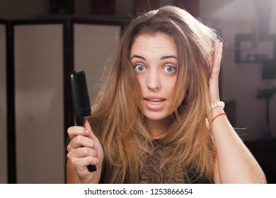 worried young pretty brown haired girl standing in a beauty salon touching flowing disheveled hair holding a brush