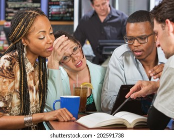 Worried young student with friends studying in cafe