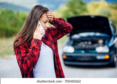Worried Young tall white caucasian woman in red plaid shirt calling for help after her car broke down in the forest near the road