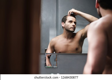 A worried young white man looks at himself in the mirror and inspects his premature receding hairline. Attractive Caucasian male adult in his 20s concerned about losing hair. Male pattern baldness