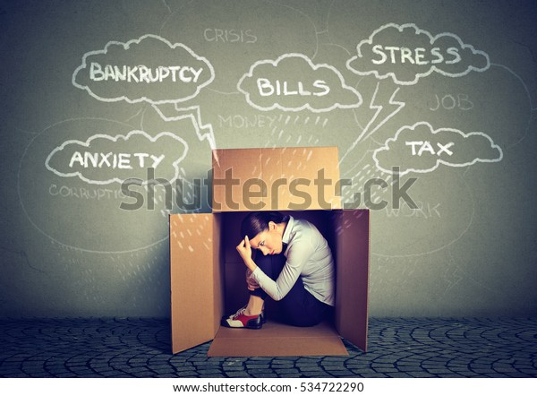 Worried young woman hiding from stress inside box