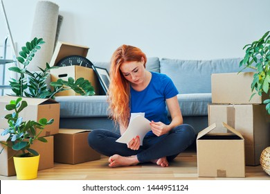 Worried young woman looking through apartment rent agreement