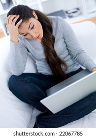 Worried young woman sitting on couch and working on laptop