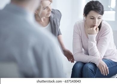 Worried young woman sitting on a group therapy