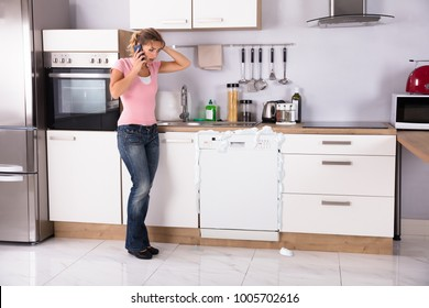 Worried Young Woman Talking On Mobilephone In Kitchen