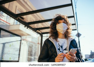 Worried young woman wearing medical face mask standing at public transport stop in European city and holding her smart phone looking for bus to come.