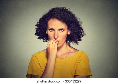 Worries. Closeup portrait nervous looking woman biting her fingernails craving something anxious isolated on gray wall background. Negative human emotion facial expression body language perception