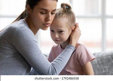 Worrying young mother comforting little stressed crying daughter, head shot. Loving mommy apologizing to offended small kid girl, stroking her head, showing care indoors, family conflict concept.