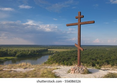 Worship Christian cross on the edge of the steep banks of the great river