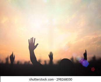 Worship concept: Silhouette christian people hand rising over blurred cross on spiritual light background