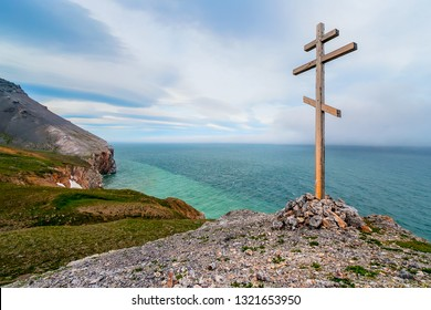 Worship cross (wayside cross) on the coast of the Bering Strait. The surroundings of Cape Dezhnev (the most eastern point of Eurasia). Chukotka, Far East of Russia. Summer day. Beautiful sea view.