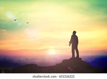 Worship God concept: Silhouette of humble business man standing on mountain autumn sunset background