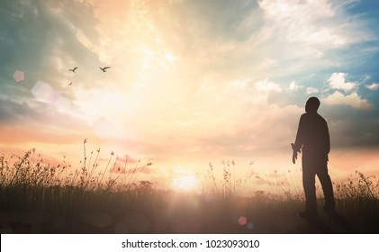 Worship and praise God concept: Silhouette humble man standing on sunlight with meadow autumn sunset background