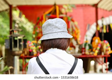 the worshipers praying and blessing in front of spirit house (joss house) in thailand.