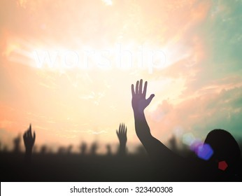 Worshiping God concept: Silhouette people raising hands over blurred text for WORSHIP on beautiful nature background