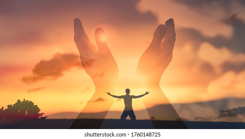 Worshiping hands raised up with open palms to the sunset sky.  Christian Religion concept background. Faith, hope, and prayer concept.