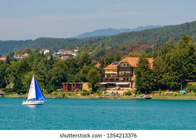 WORTHERSEE, AUSTRIA - AUGUST 08, 2018:  Worthersee view at turquoise water of lake in summer mountains in distance. Tourists enjoying summer vacations.