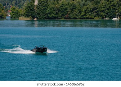 WORTHERSEE, AUSTRIA - AUGUST 08, 2018: View from the boat to the lake and coastline. Local residents and tourists swim, driven by motorboats and use other forms of water recreation.