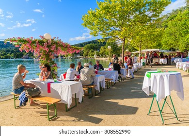 WORTHERSEE LAKE, AUSTRIA - JUN 20, 2015: people sitting at tables along Worthersee lake shore during summer beer festival.