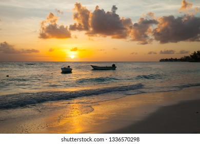 Worthing beach in Barbados at sunset. Two boat in the foreground. Carribean sea