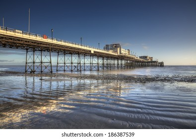 Worthing Pier reflected in wet sand at low tide, illuminated by late afternoon sunshine.