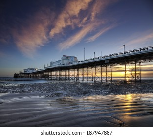 Worthing Pier reflected in wet sand at low tide, illuminated by a beautiful sunset.