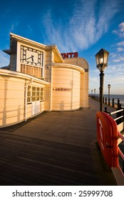 Worthing pier at sunset with clock and amusements