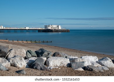 Worthing Pier, West Sussex view of the pier with a silky calm sea on a warm and clear day in Autumn.