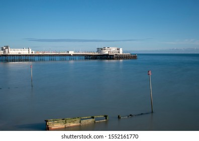 Worthing Pier, West Sussex view of the pier and wooden breakwater with a silky calm sea on a warm and clear day in Autumn.