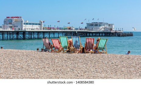 Worthing, Sussex, UK; 14th July 2018, Rear View of Group of People Seated in Six Striped Deckchairs at the Seaside on a Bright Sunny Summer Day.  Worthing Pier in Background