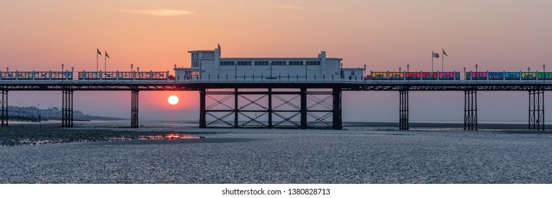 Worthing, Sussex, UK; 20th April 2019; Dawn With Sun Rising Behind Worthing Pier at Low Tide