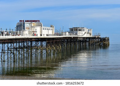 Worthing, UK - August 16 2020: Sussex 2019 pier winner provides iconic focus for the town. Tourists can view artwork promenade above the waves enjoy deckchairs treats at the Art Deco Southern Pavilion
