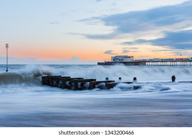 Worthing, West Sussex / UK - March 17 2019: Worthing Pier at sunset, with crashing waves in the foreground.