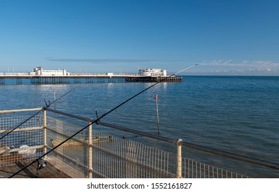Worthing, West Sussex view of the pier and fishing rods with a calm sea on a warm and clear day in Autumn.